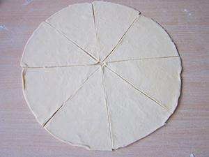 Ją iškočiojame, išpjauname apskritimą (naudojau didelę lėkštę). Apskritimui padarome 4 pjūvius, kad gautųsi trikampiai.